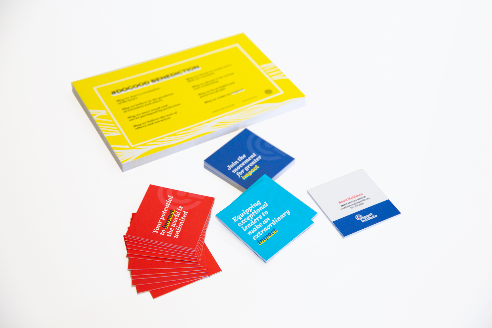 Stack of yellow postcards and scattered red, aqua, and dark blue square business cards on a white surface