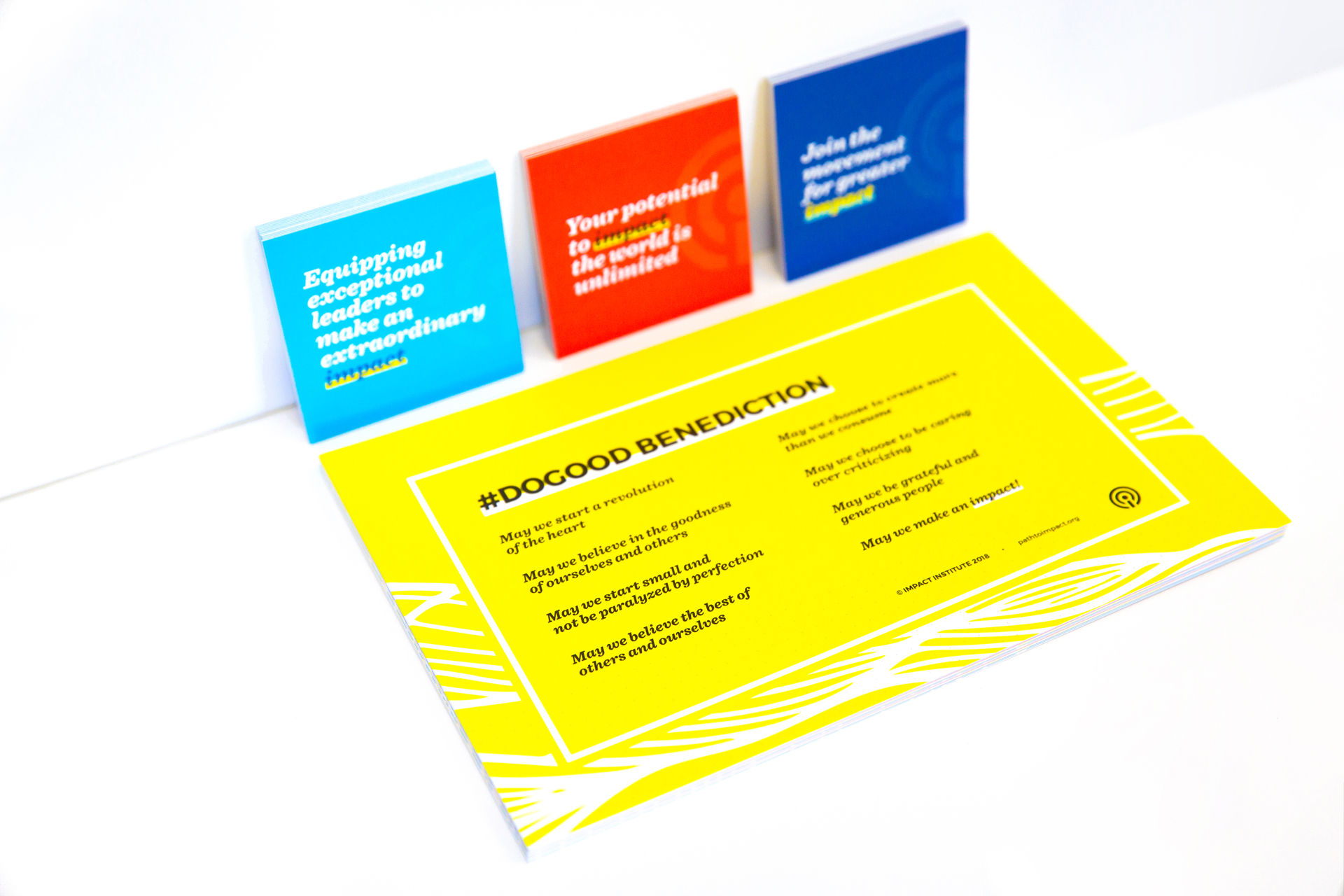 Stack of yellow postcards sitting on and red, aqua, and dark blue square leaning up against a white surface