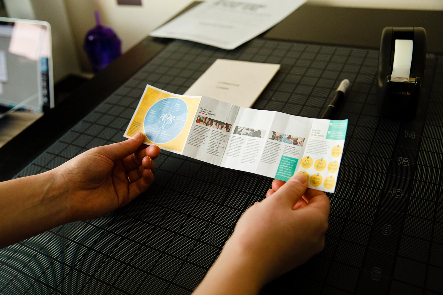 Two hands holding miniature prototype of folded brochure over black gridded background