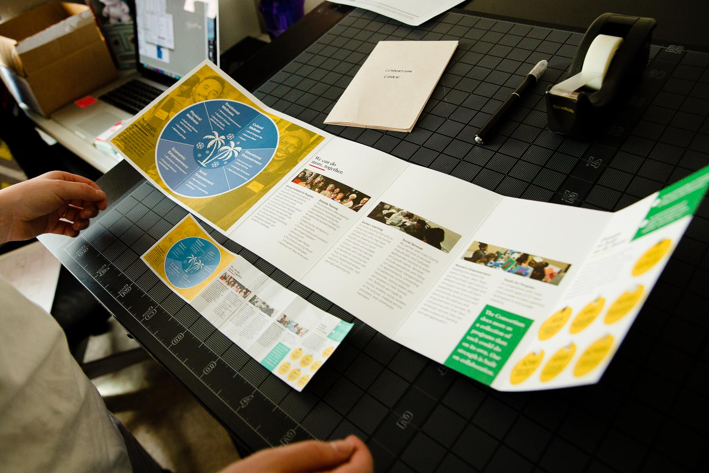 Full-size brochure next to miniature prototype of folded brochure over black gridded background