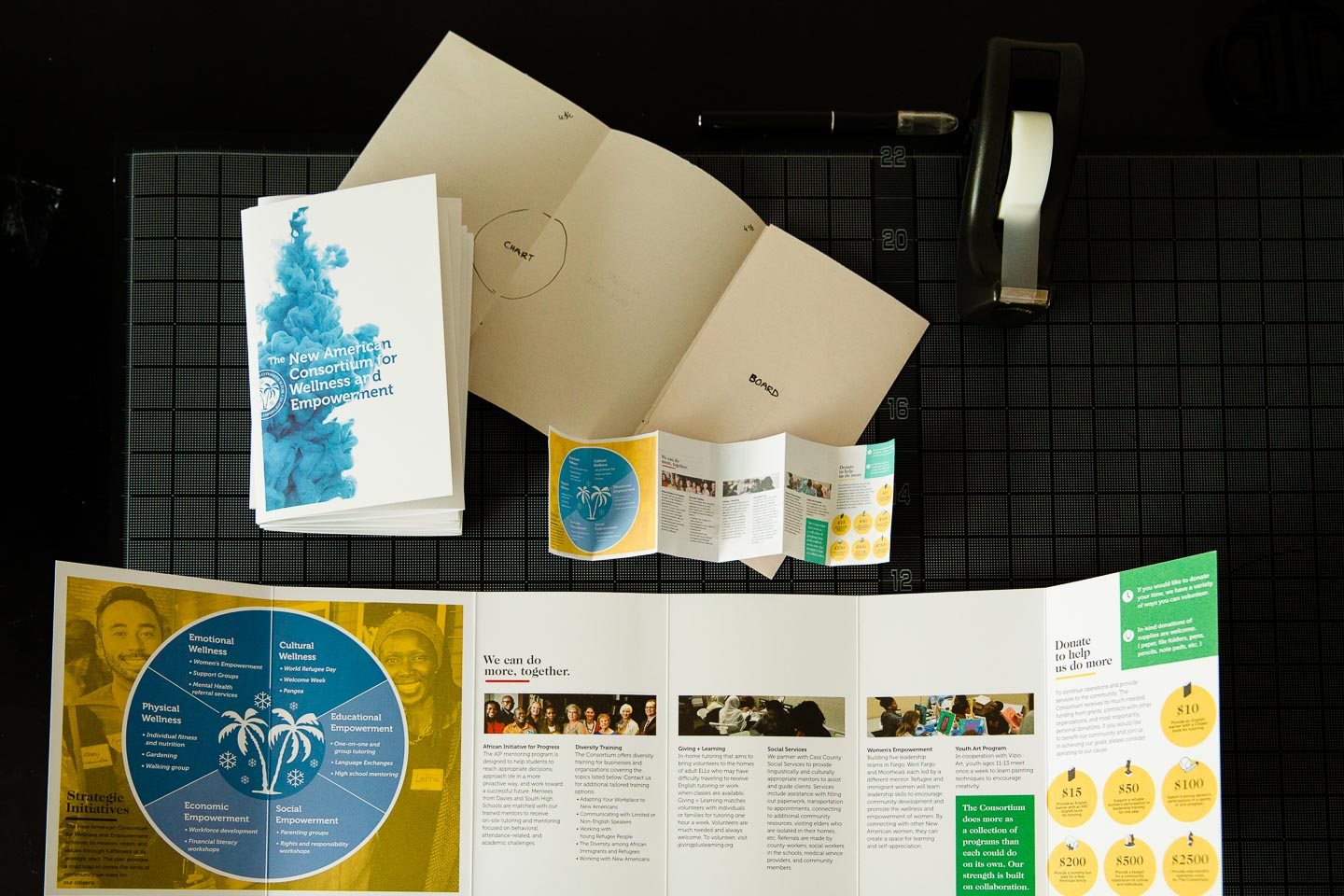 Full-size brochure next to various prototypes of folded brochure over black gridded background