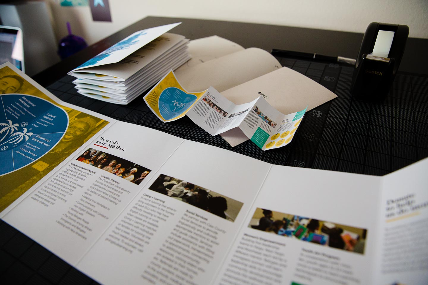 Brochure open below stack of folded brochures and miniature prototype on black gridded background