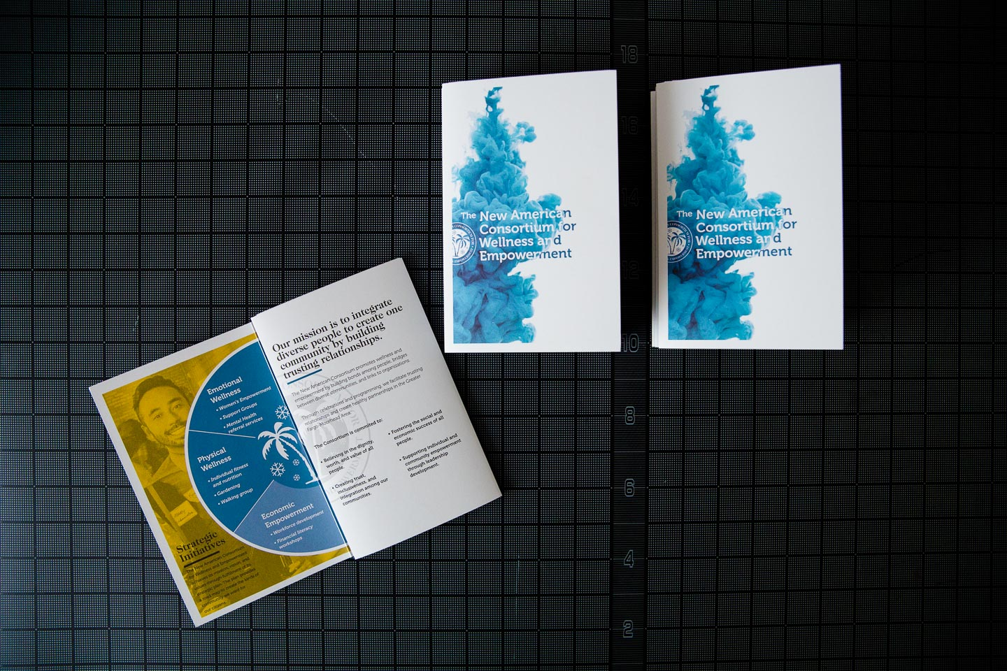One partially open brochure and two folded brochures on a black gridded background