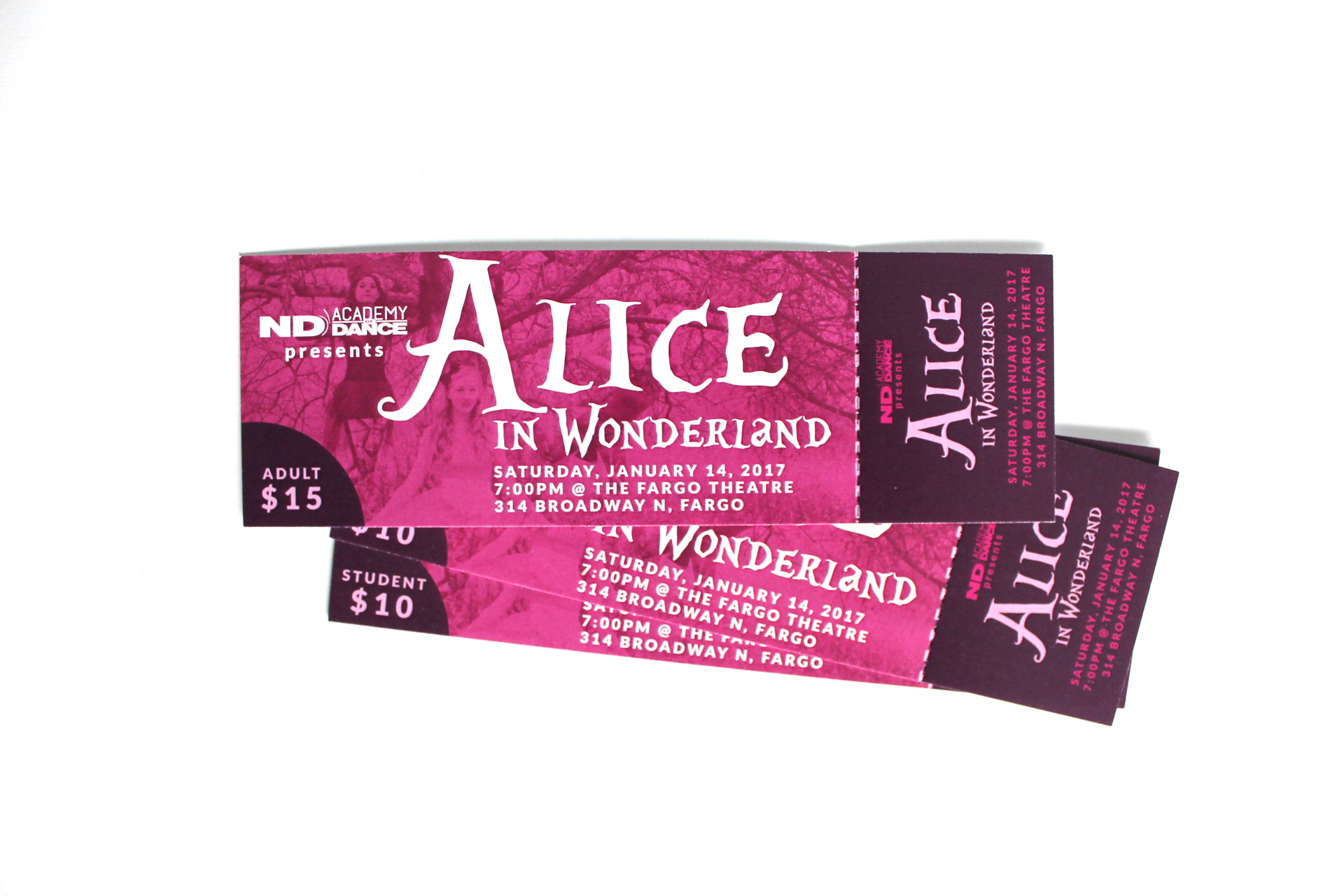 Stack of pink and purple tickets to Alice in Wonderland on a white backdrop
