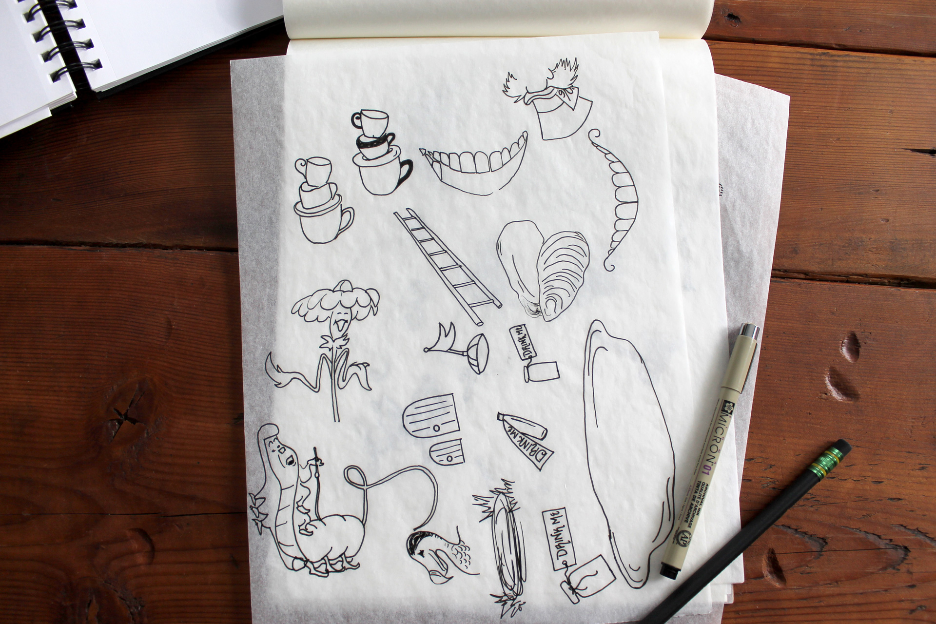 Tracing paper with sketches of animated Alice in Wonderland elements on a wood table next to a pen and pencil