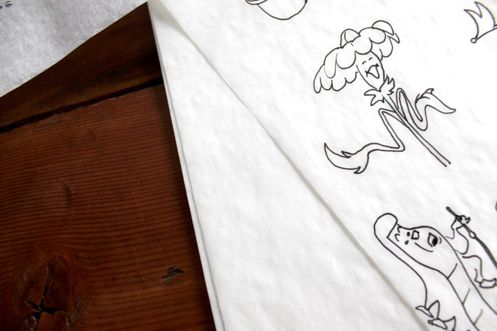Close up of illustrations on tracing paper sitting on a wooden table
