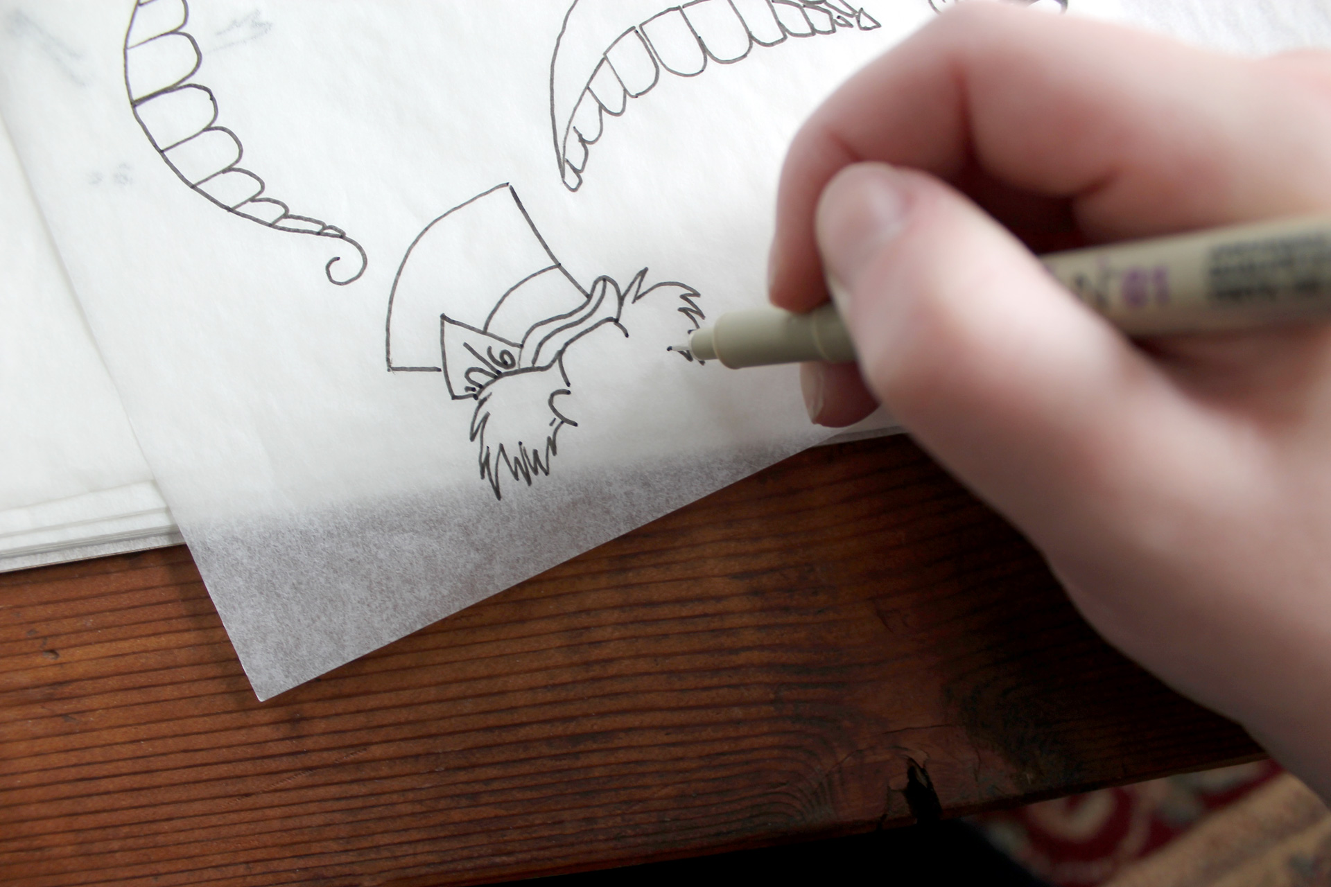 Close-up of hand drawing Mad Hatter illustration on tracing paper atop a wooden table