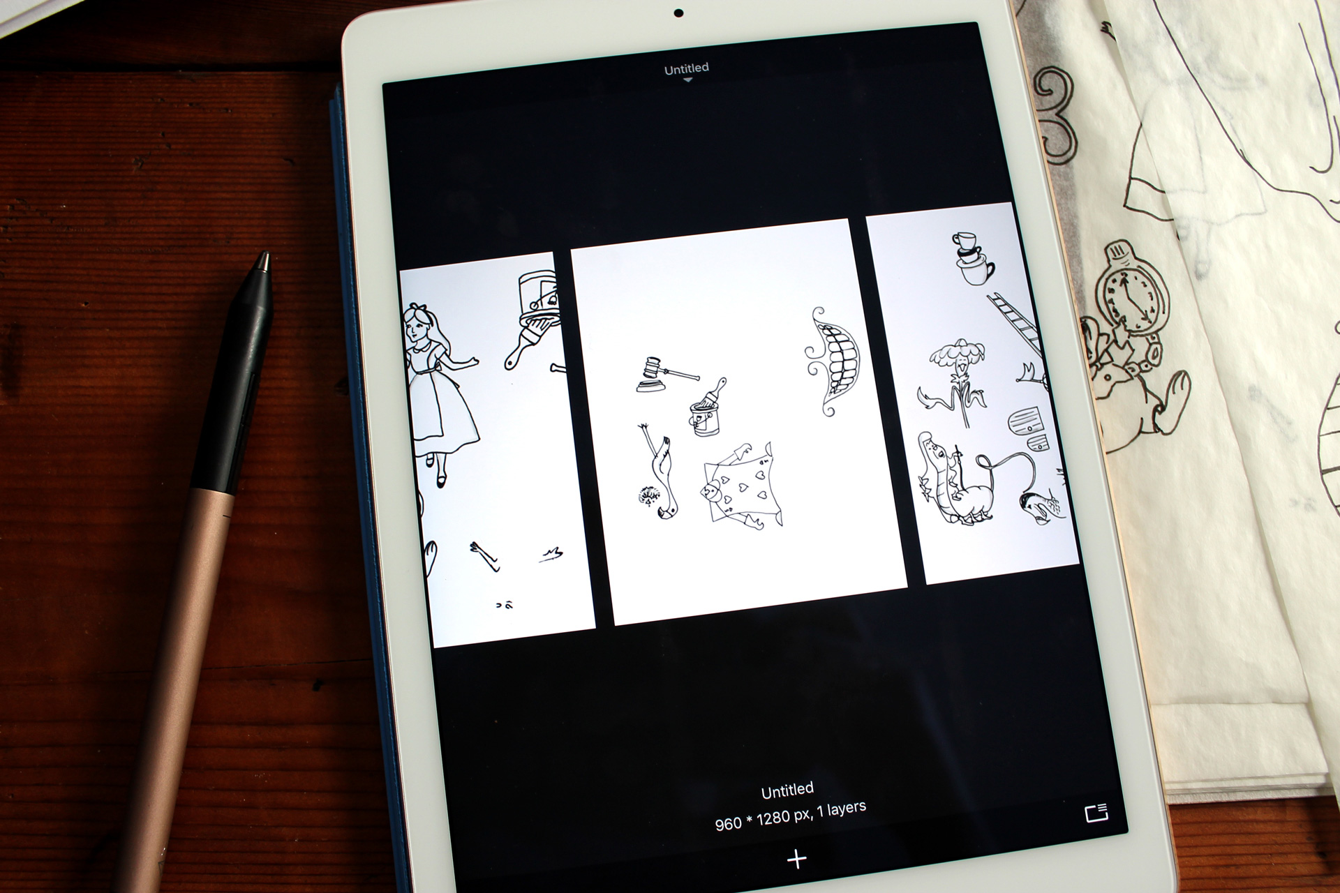 iPad showing sketches next to tracing paper and a gold stylus