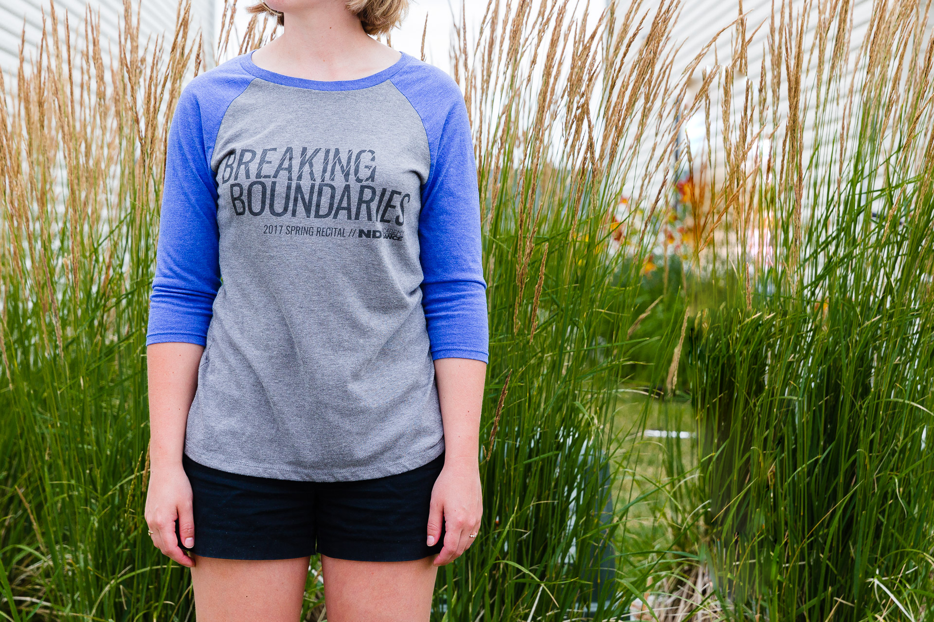 Girl standing in front of tall grass wearing a gray baseball tee with blue sleeves with the words Breaking Boundaries on it