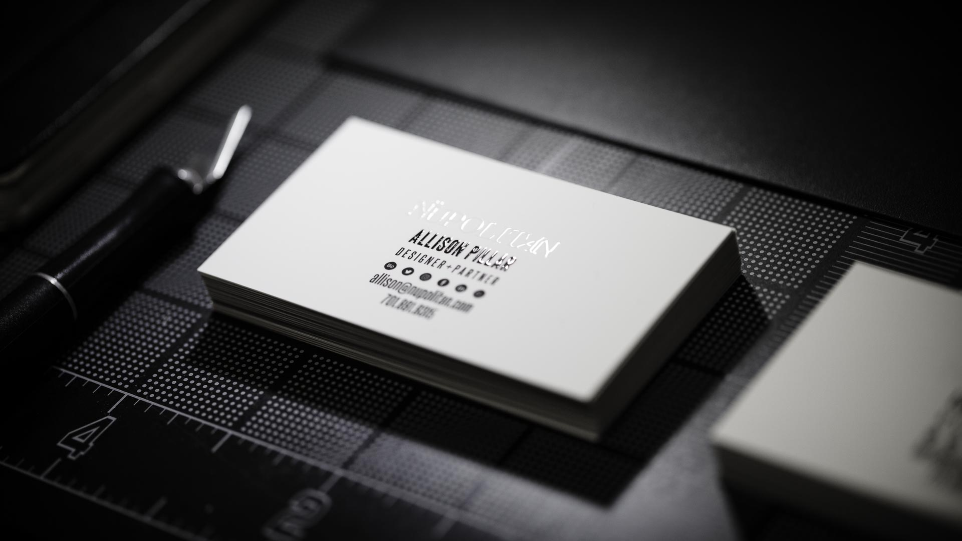 Stack of white business cards with black text and Nüpolitan printed in spot gloss