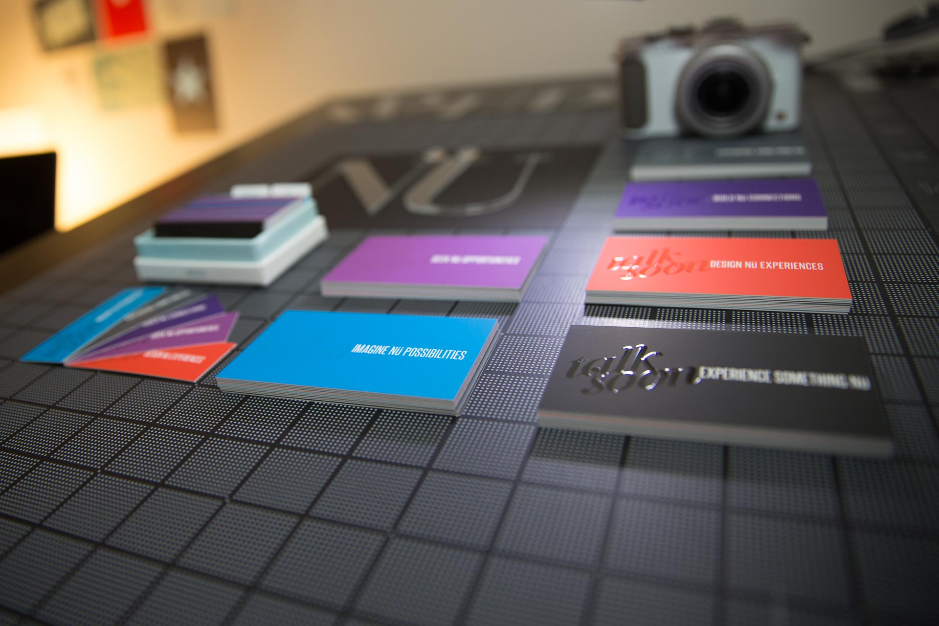 NÜ in acrylic letters, a white camera, and purple, blue, and red business cards on a black gridded surface