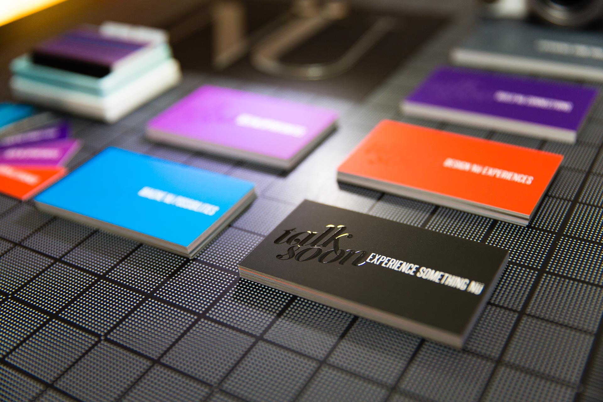 Close-up of black business card with spot gloss with colored cards in the background