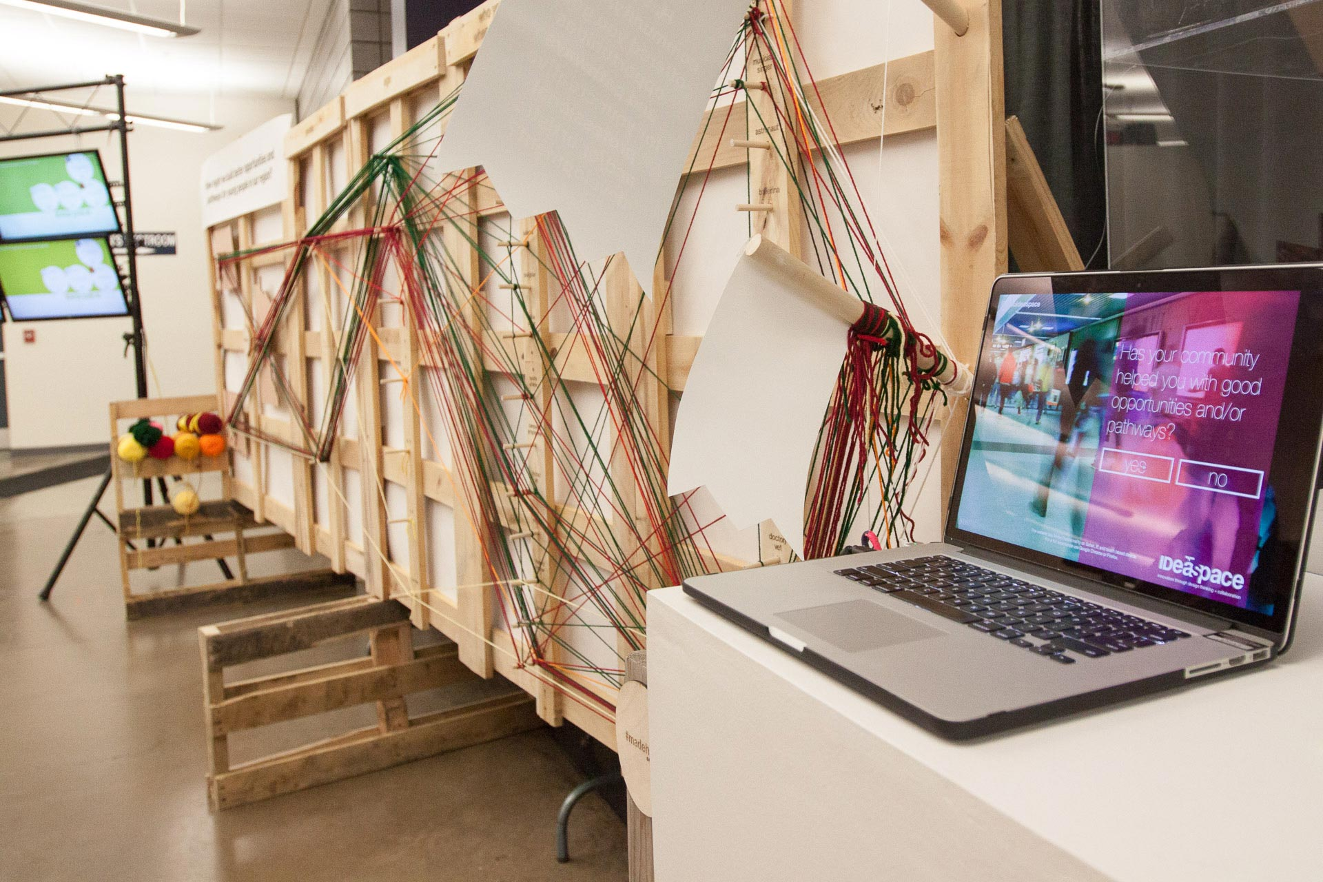 Laptop on white table in front of wood and yarn installation