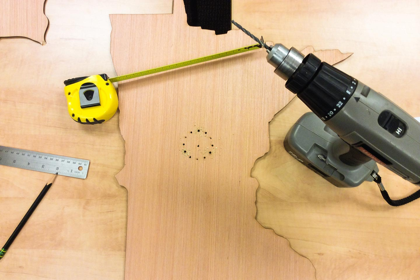Drill, tape measure, and wood in the shape of Minnesota