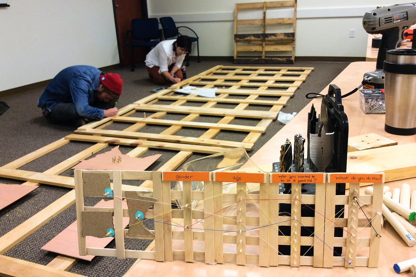 Two people assembling wooden structure with small prototype in the foreground