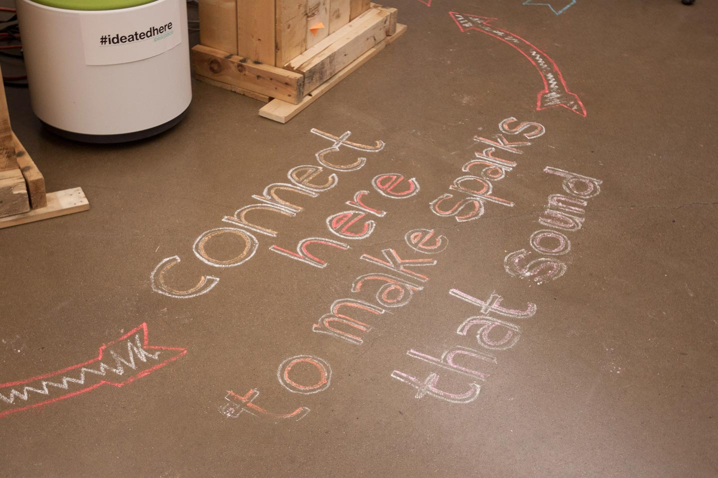 Chalk on concrete floor that reads: connect here to make sparks that sound