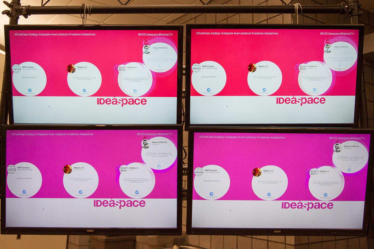 Four TV screens displaying interactive installation digital interface in pink and red
