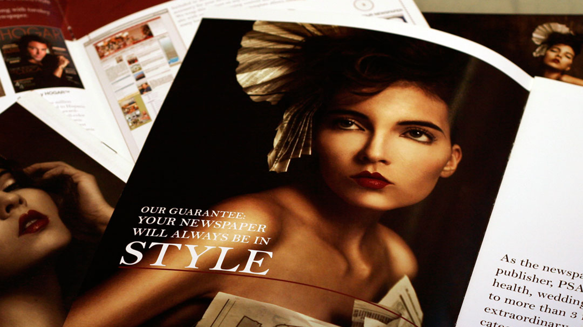 Magazine open to photo of woman wearing newspaper dress and hat on top of other open magazines