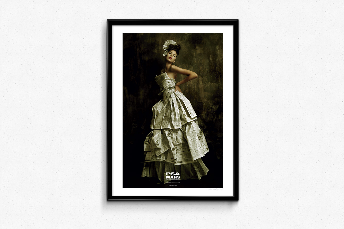 A single, framed poster of a woman dressed in a high-fashion dress made of newspaper