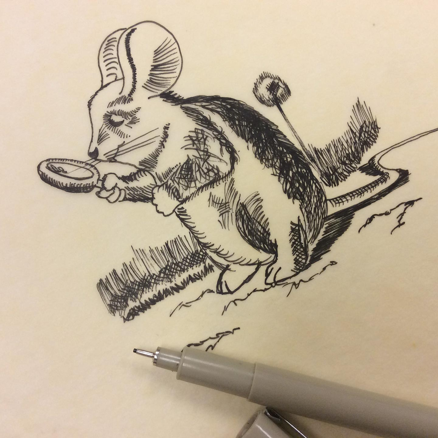 Close-up of a pen and a sketch of a mouse holding a magnifying glass