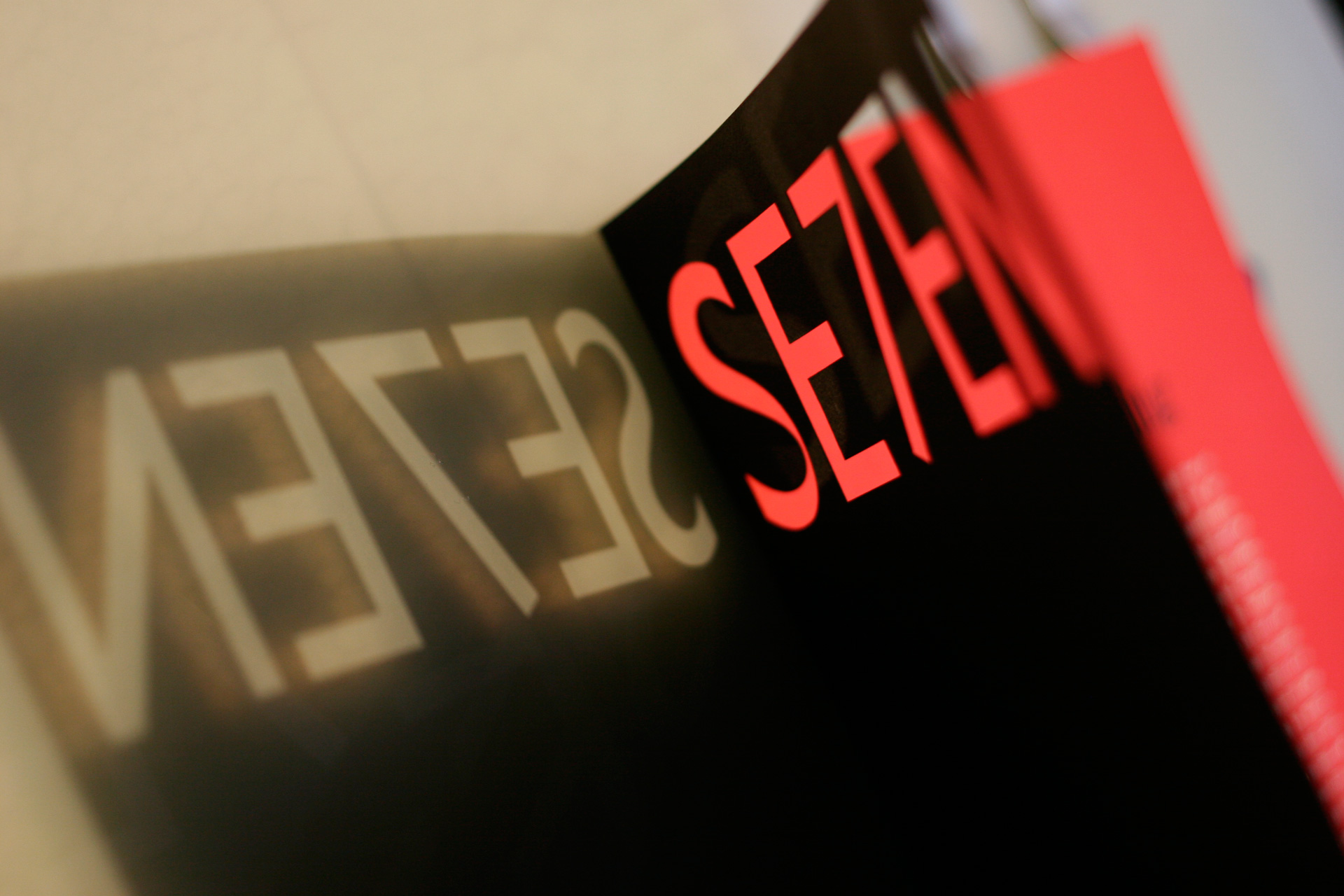 Light reflecting through a cutout of the word SE7EN on black cover of magazine with red interior