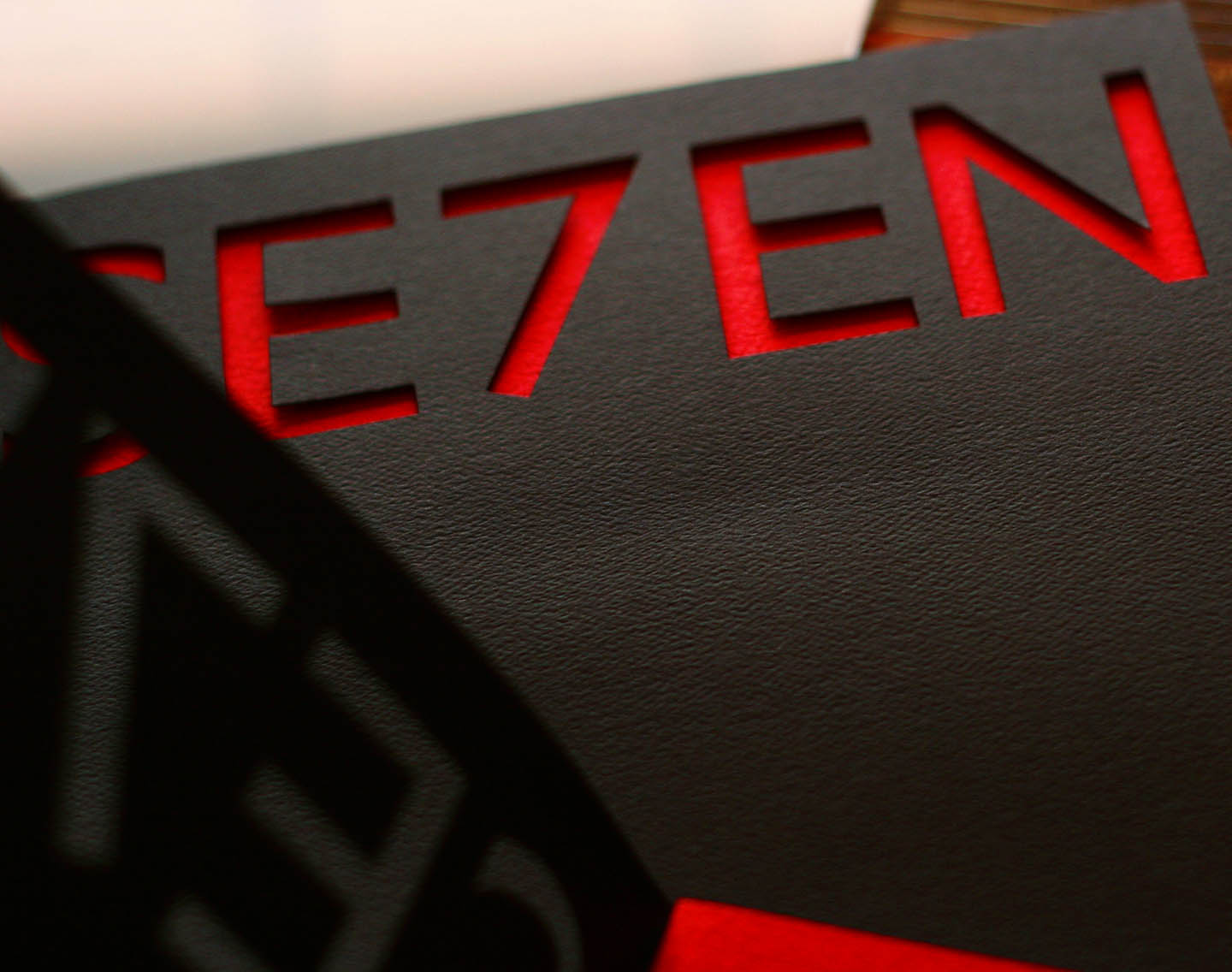 A cutout of the word SE7EN on black cover of magazine with red interior