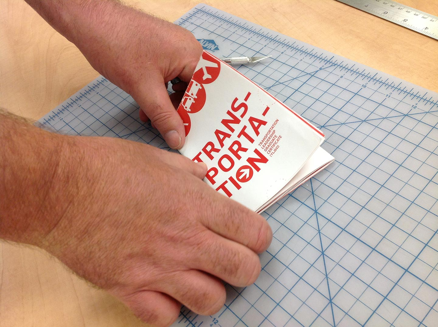 Two hands folding a transportation brochure atop a light blue gridded cutting mat