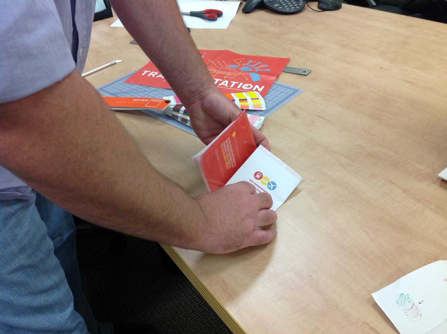 Two hands folding a transportation brochure atop a light wood table