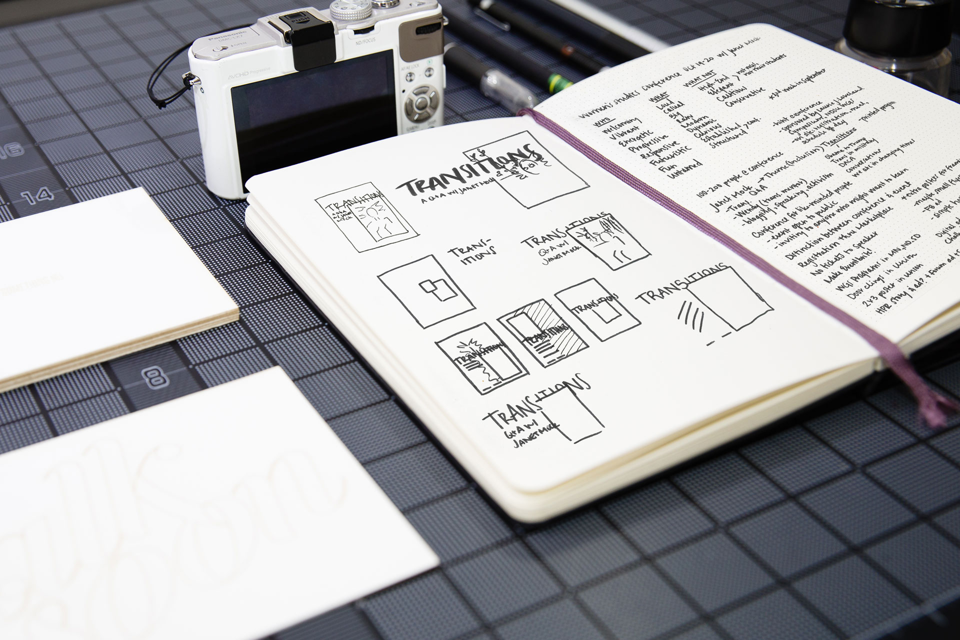 Sketchbook of design concepts next to a white camera and white cards atop a black gridded surface