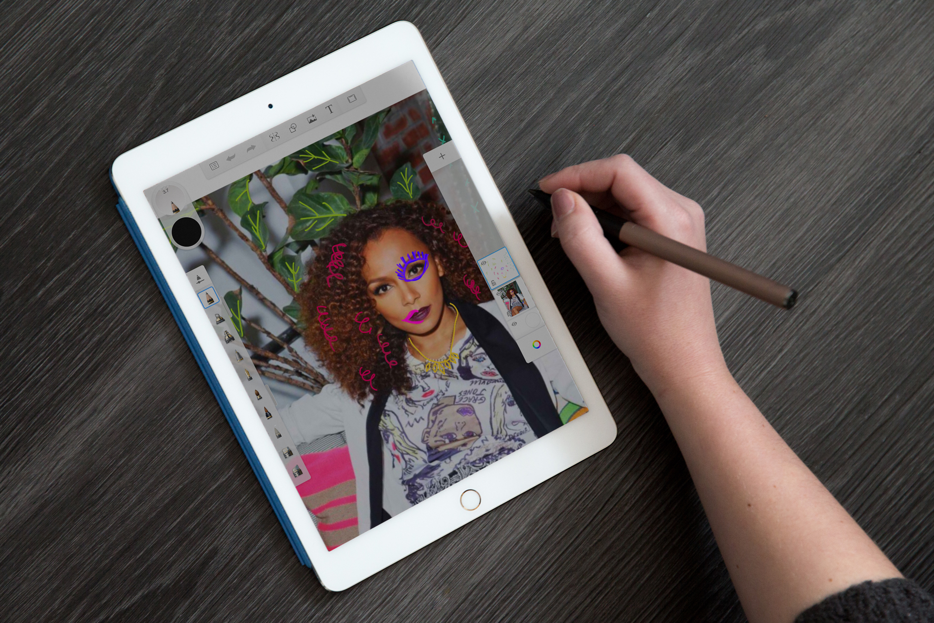 A woman's hand sketching illustrative details on an iPad