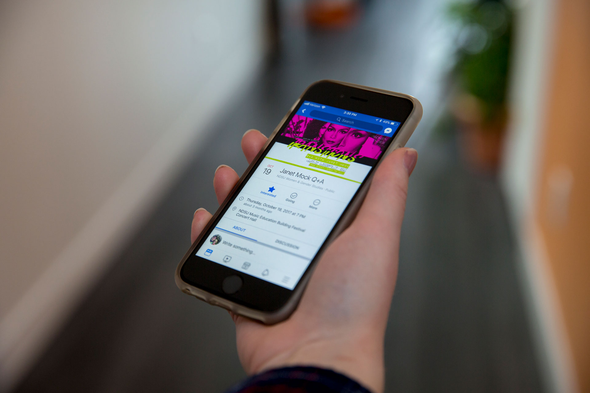A hand holding an iPhone displaying a Facebook event with pink and green cover photo