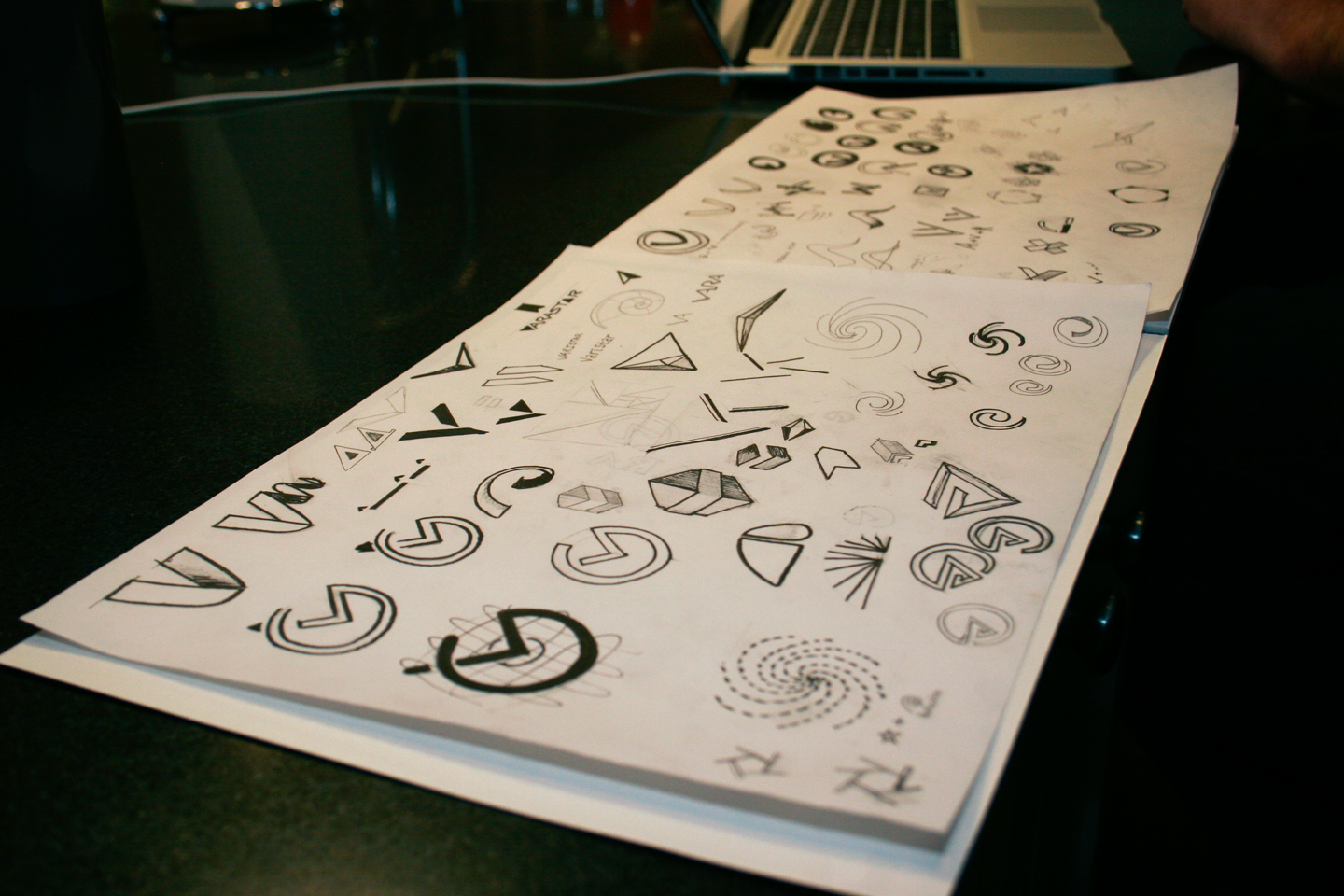Sketchbook pages displaying hand-drawn logo concepts for Varistar
