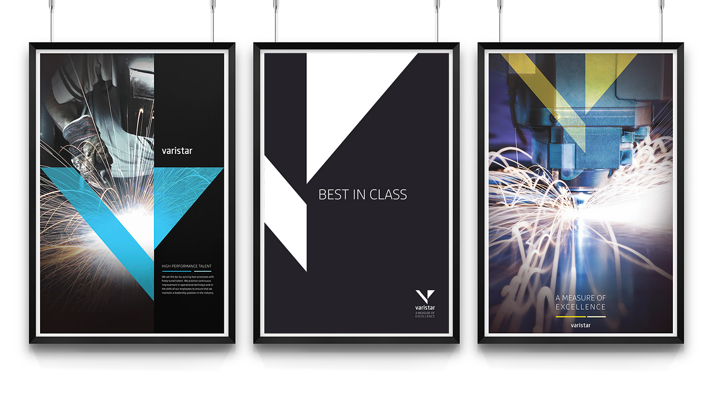 Three framed Varistar posters displaying the logomark and blue and white sparks on a black background