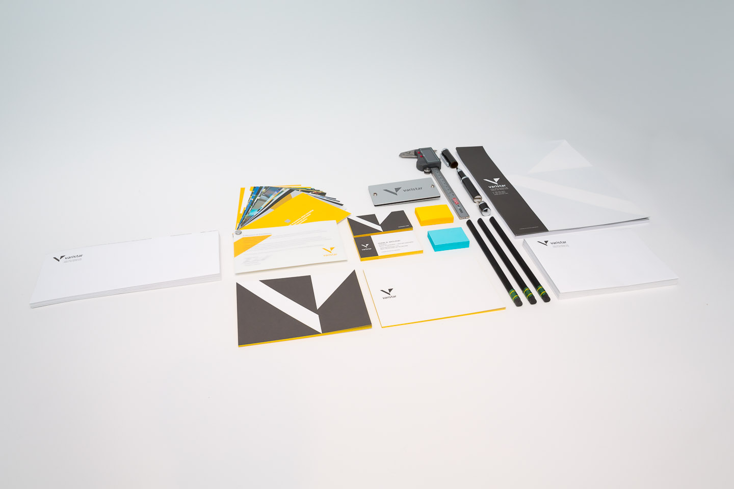 Gray, yellow, and blue letterhead, postcards, business, cards, and colored post-it notes atop a white surface