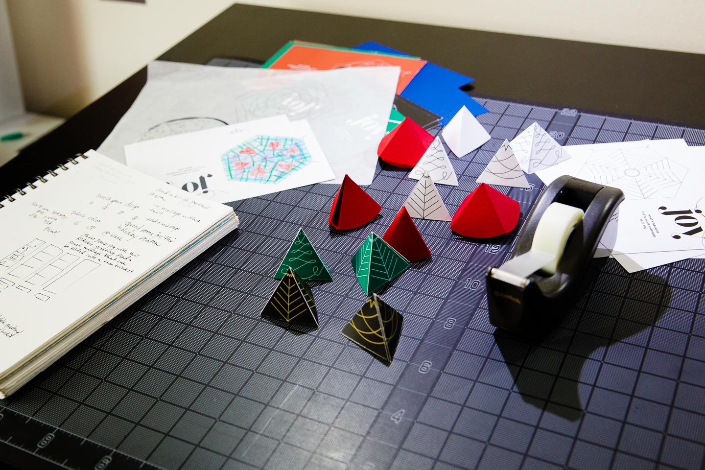 Small triangular paper prototypes in red, green, and black atop a black gridded cutting mat