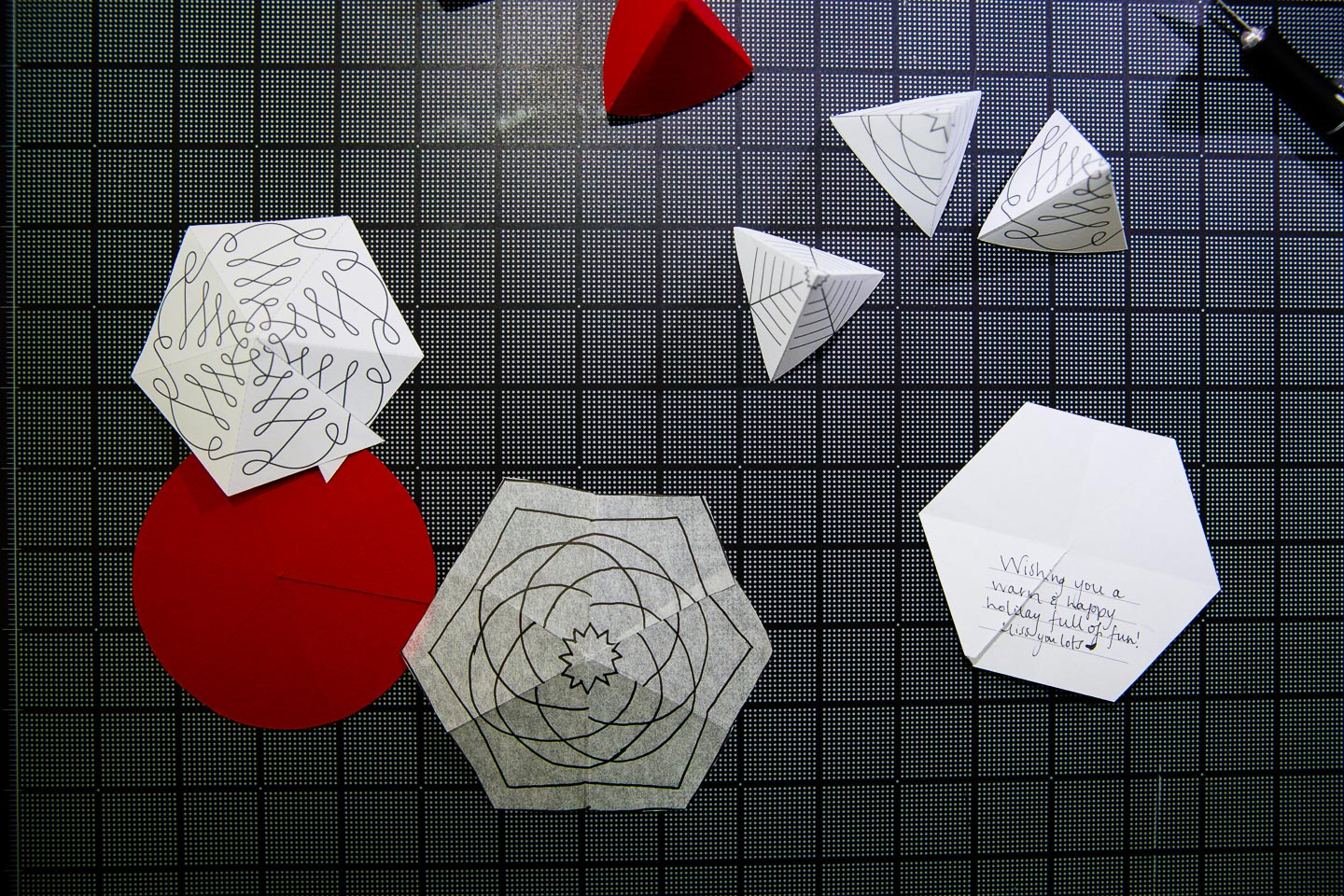 Red and white paper hexagons and small 3D paper trees sitting on a black gridded cutting mat