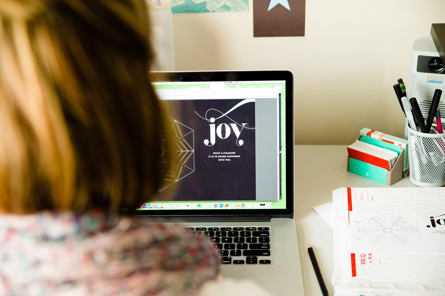 A woman working on a laptop creating a black postcard that reads Joy next to a circular pattern