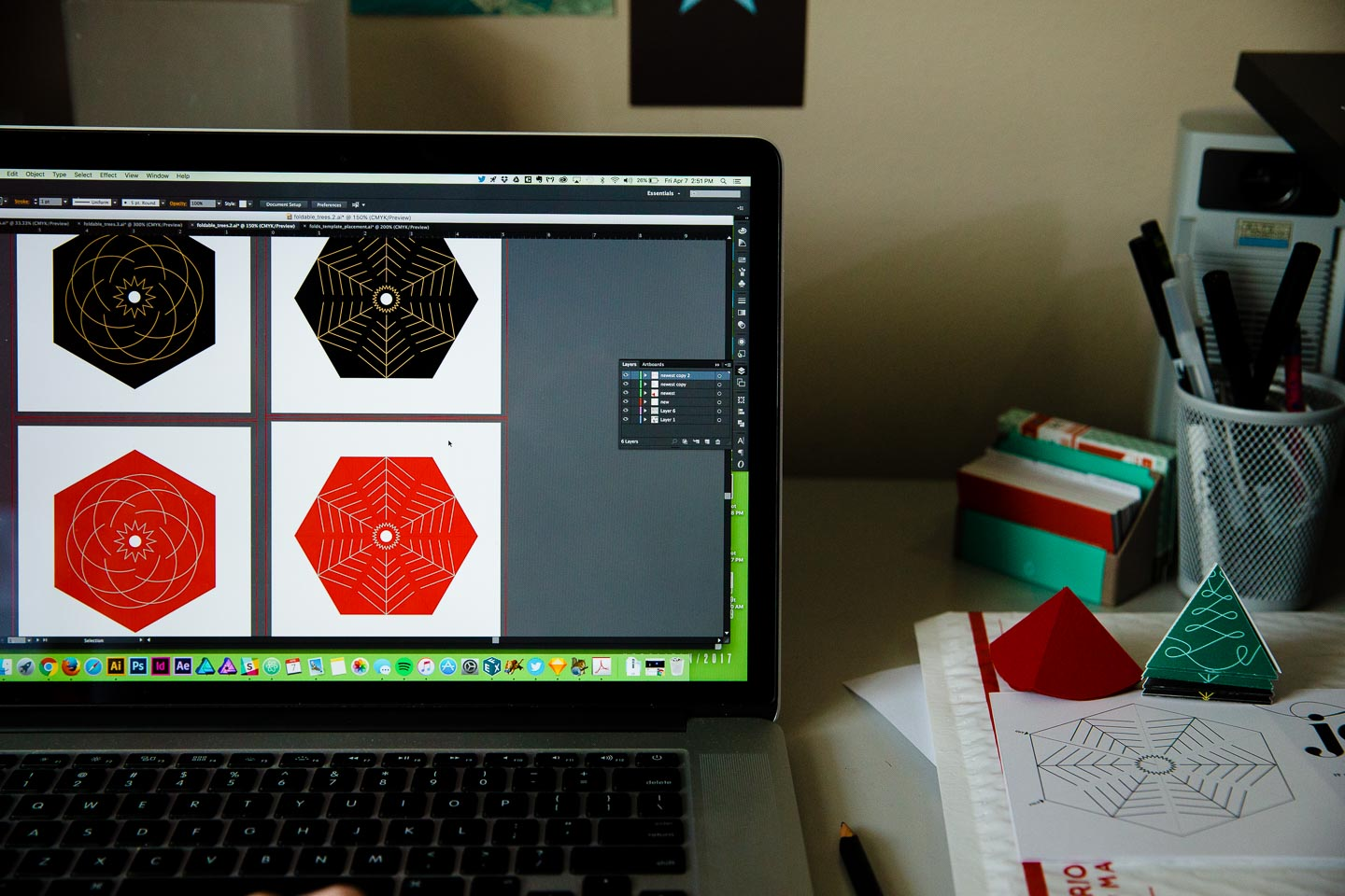 A laptop screen displaying four hexagons in black and red