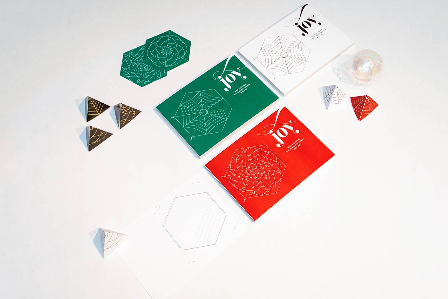 Wunderfold in its card form, punched out hexagon form, and folded 3D tree form in green, red, and black