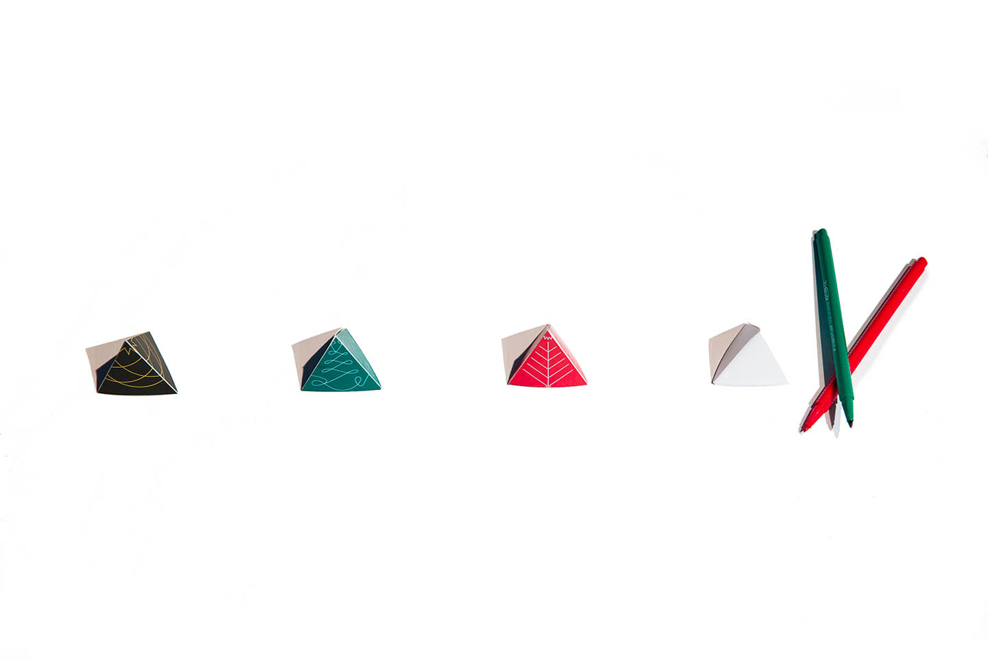 Black, green, red, and white 3D folded trees next to red and green markers on a white surface