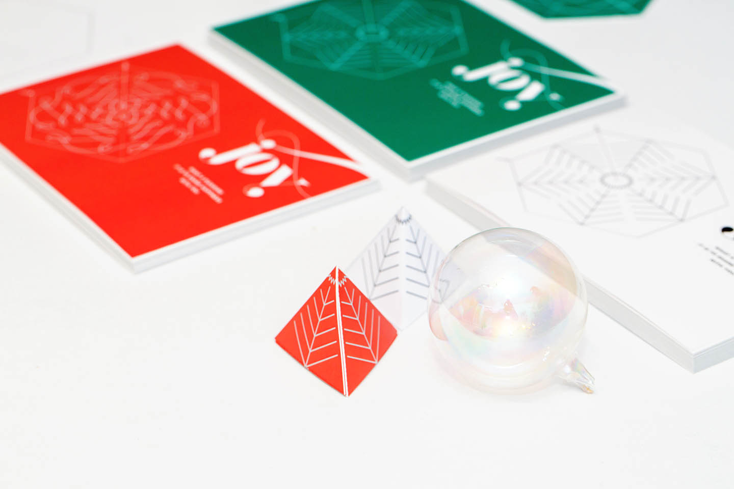 Wunderfold in its card form, punched out hexagon form, and folded 3D tree form in green and red