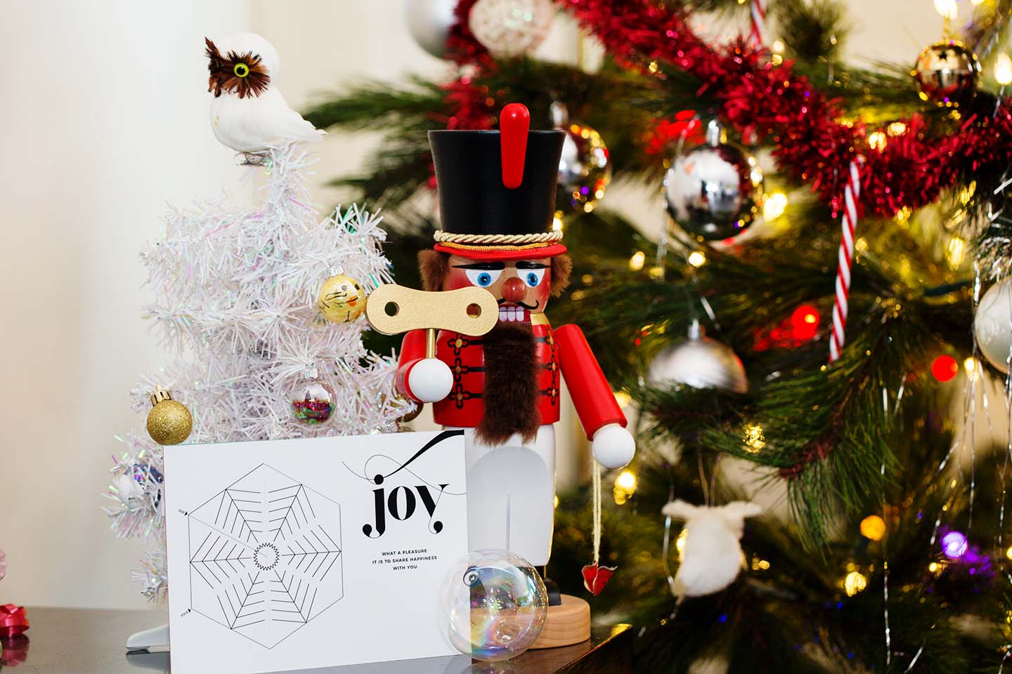 A white Wunderfold card with the word Joy on it next to a nutcracker and tree in front of a large Christmas tree