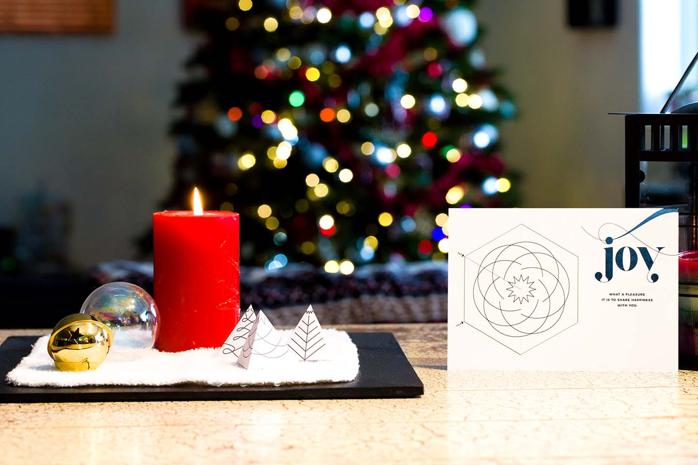 A white Wunderfold card with the word Joy on it next to a candle in front of a lit Christmas tree